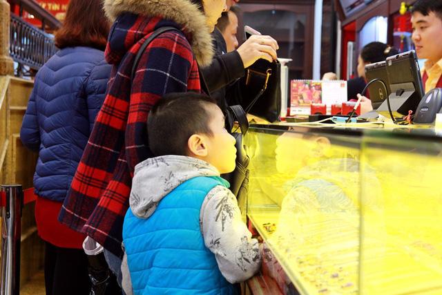 Ánh mắt tò mò của cậu bé khi lần đầu được cùng mẹ đi xếp hàng chờ mua vàng