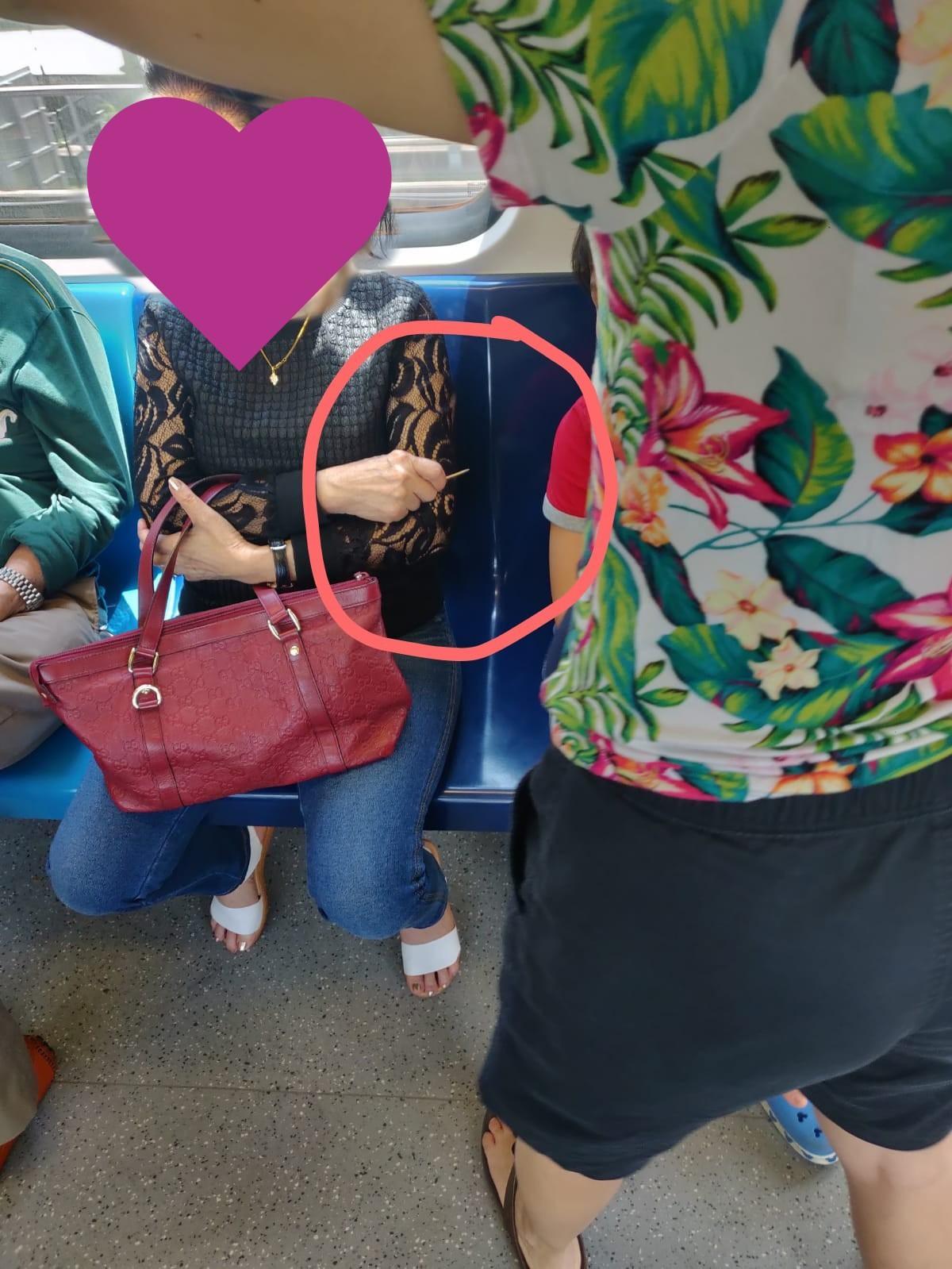 Bức ảnh người phụ nữ cầm cây tăm trên tay, bên cạnh là bé trai đang ngủ gật để tránh đứa trẻ động vào người gây tranh cãi - Ảnh 1.