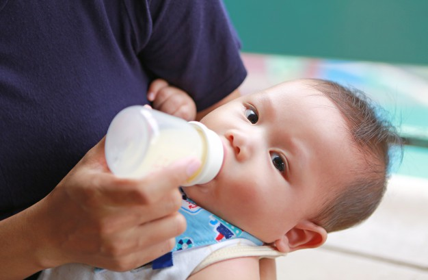 close-up-asian-newborn-drinking-milk-from-bottle-by-mother_38678-2851