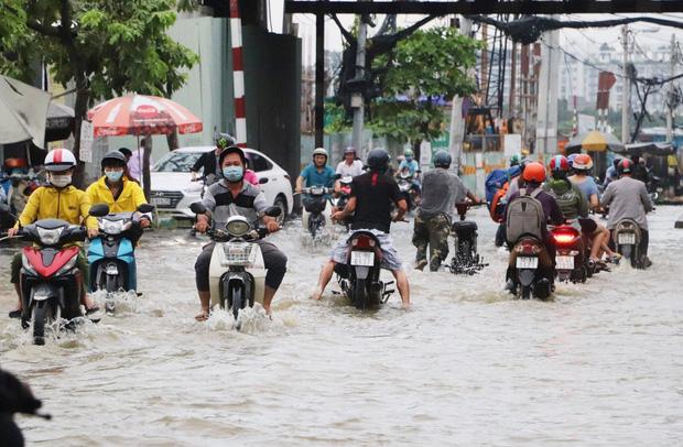 Hết dầm mưa liên tiếp, dân Sài Gòn lại khốn khổ vì triều cường đạt đỉnh, bì bõm dắt xe qua đường ngập - Ảnh 1.
