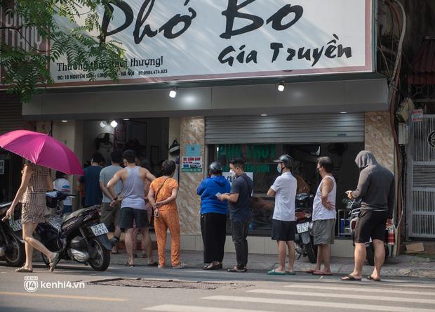 Xếp hàng dài mua đồ ăn ở Long Biên (Hà Nội): Khách mang cả cái nồi to, chủ quán làm 500 tô/ngày vẫn không đủ bán - Ảnh 1.